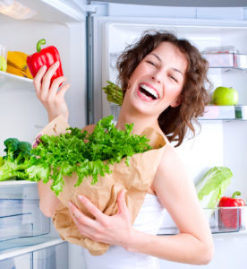 Dieting concept .Diet. Beautiful Young Woman near the Refrigerator with healthy food. Fruits and Vegetables