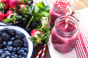 Well being and weight loss concept berry smoothie.On wooden table with ingredients from above. ** Note: Shallow depth of field