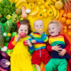 Boy girl and baby with variety of fruit and vegetable. Colorful rainbow of raw fruits and vegetables. Child eating healthy snack. Vegetarian nutrition for kids. Vitamins for children. View from above