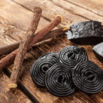 Production steps of licorice roots pure blocks and candy on wooden table ** Note: Shallow depth of field