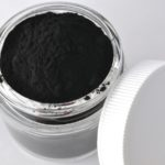 Powdered activated charcoal for facial mask in jar with copy space